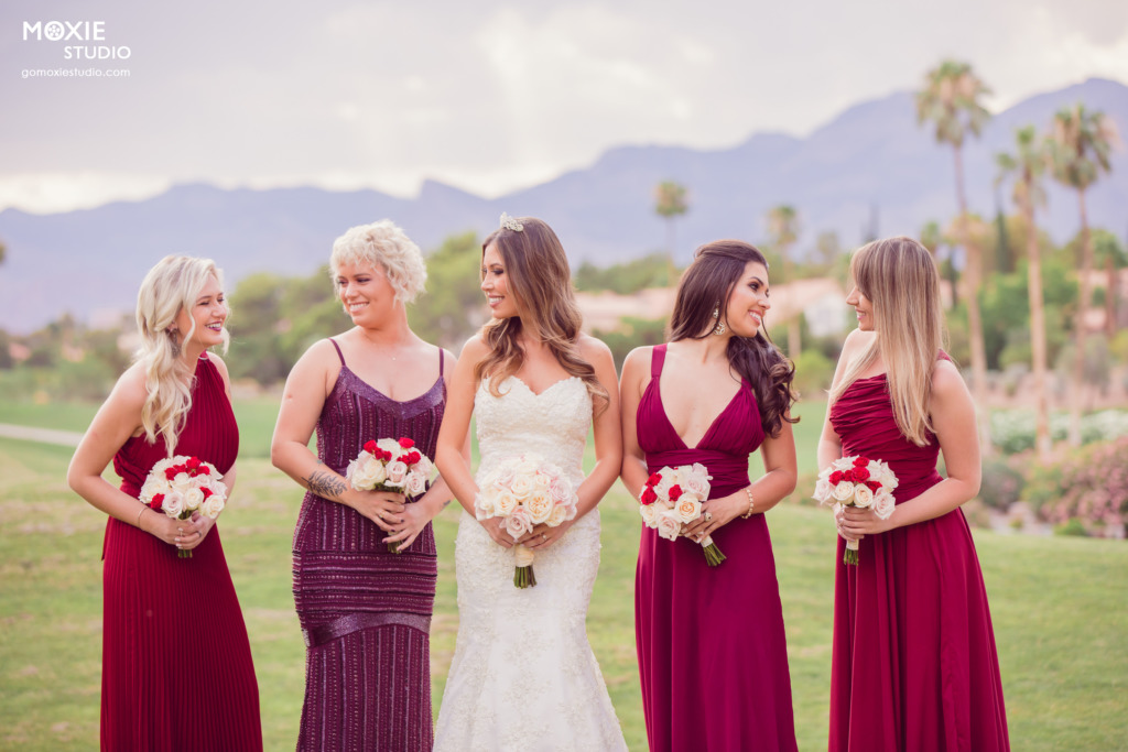 bridesmaids in red dresses with bride on the lawn of a golf course. photo by moxie studio