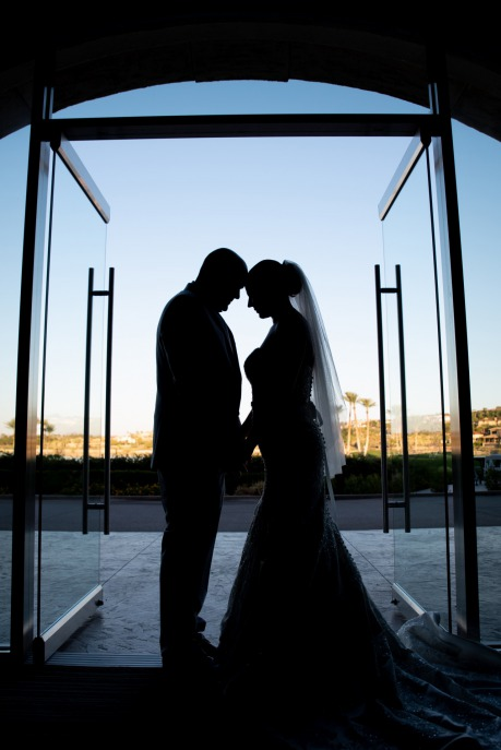 Silhouette of Bride and Groom touching foreheads in doorway