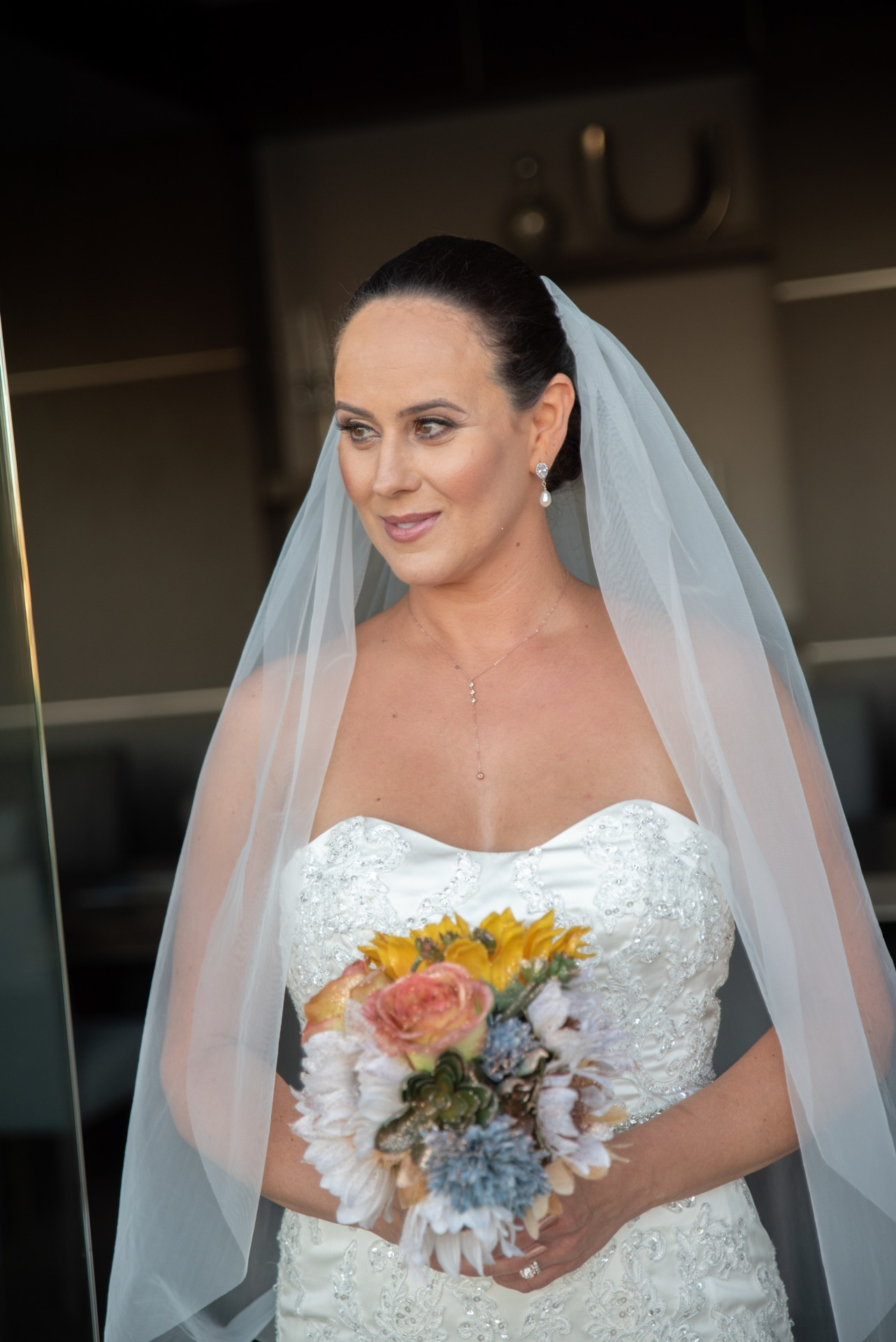 Beautiful Las Vegas bride wearing wedding dress with sweetheart neckline and holding bouquet with orange roses.