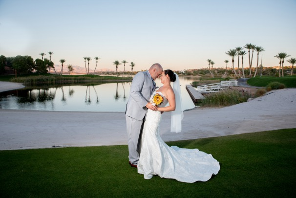Happy Couple poses for photos at reflection bay golf with stunning greens and waterfalls in the background