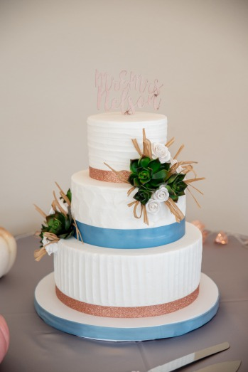 Blue Fall Wedding Inspiration. White three tier wedding cake accented with coral and dusty blue ribbon. Succulents and flowers adorn the cake and it sits on a tables surrounded by white and coral pumpkins