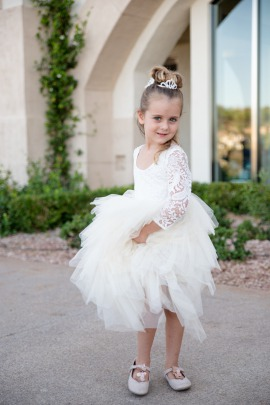 cute flower girl in a lace long sleeve dress with a full tulle skirt at a Las Vegas Wedding