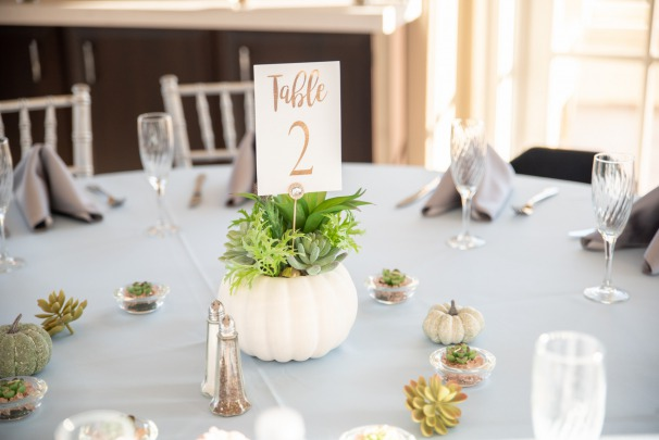 Blue Fall Wedding Inspiration. cute wedding details. white pumpkin centerpiece with lovely fresh greenery and a table sign sit on dusky blue table linens