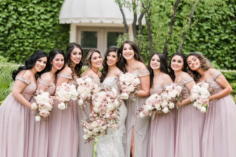 Happy Bride with her Bridesmaids who are in stunning dusty rose off the shoulder Bridesmaid gowns holding white and pink bouquets.
