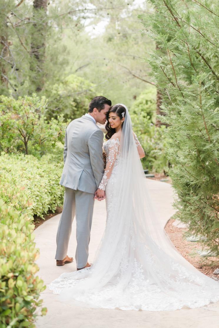 Happy bride and groom just married embracing on the beautiful outdoor property of Las Vegas JW Marriott Resort & Spa.