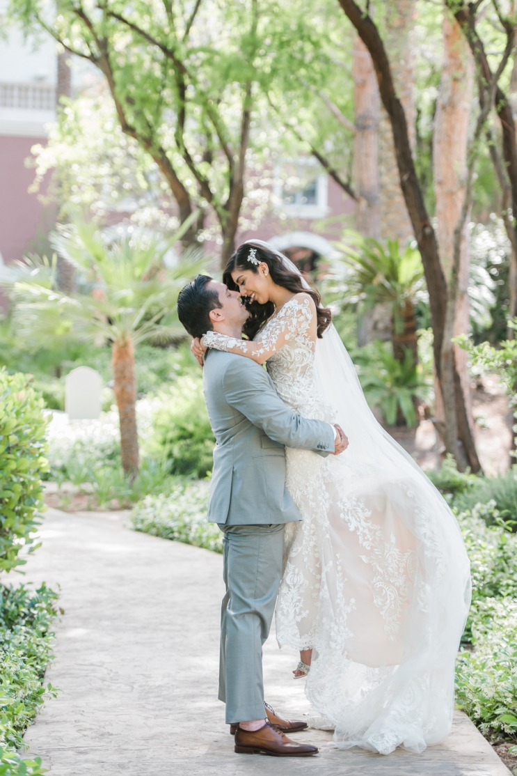 Happy bride and groom just married embracing on the beautiful outdoor property of Las Vegas JW Marriott Resort & Spa