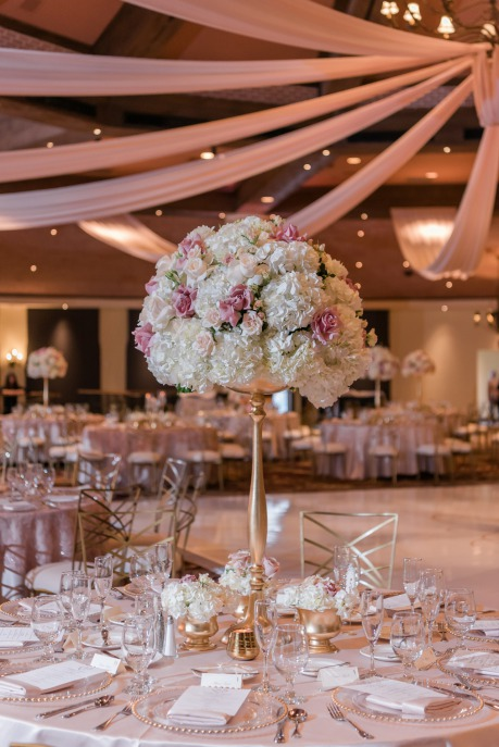 Stunning wedding reception centerpiece at the Las Vegas JW Marriott Resort adorned with lots of dusty rose and white colored roses. inside a tall golden trumpet vase.