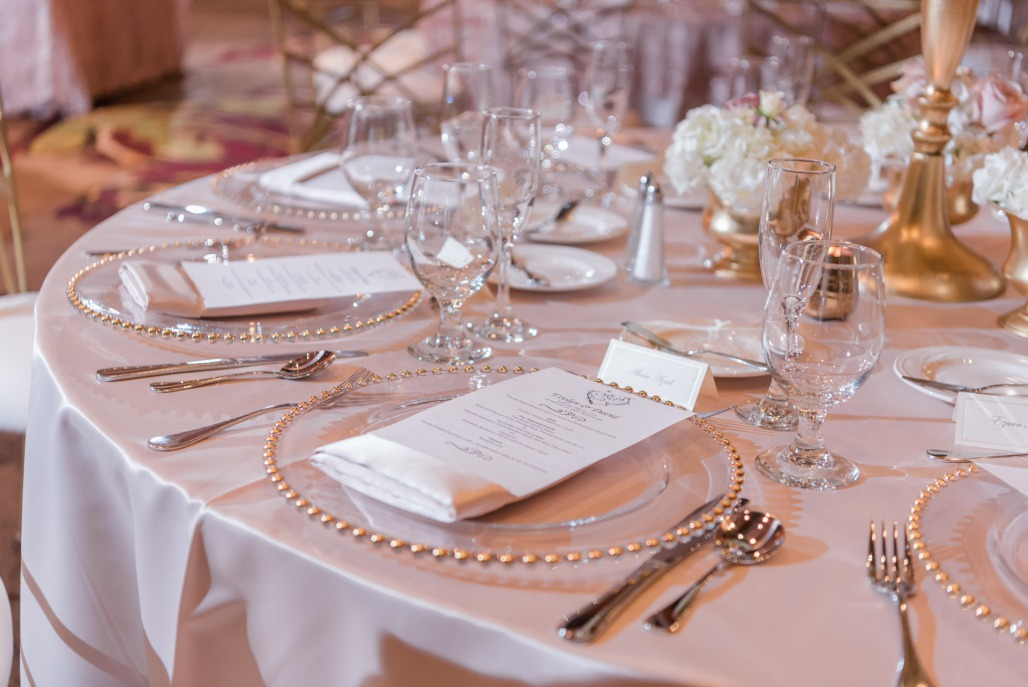 Beautiful wedding reception table setting with dusty rose table linens, modern plates, and gold tableware.