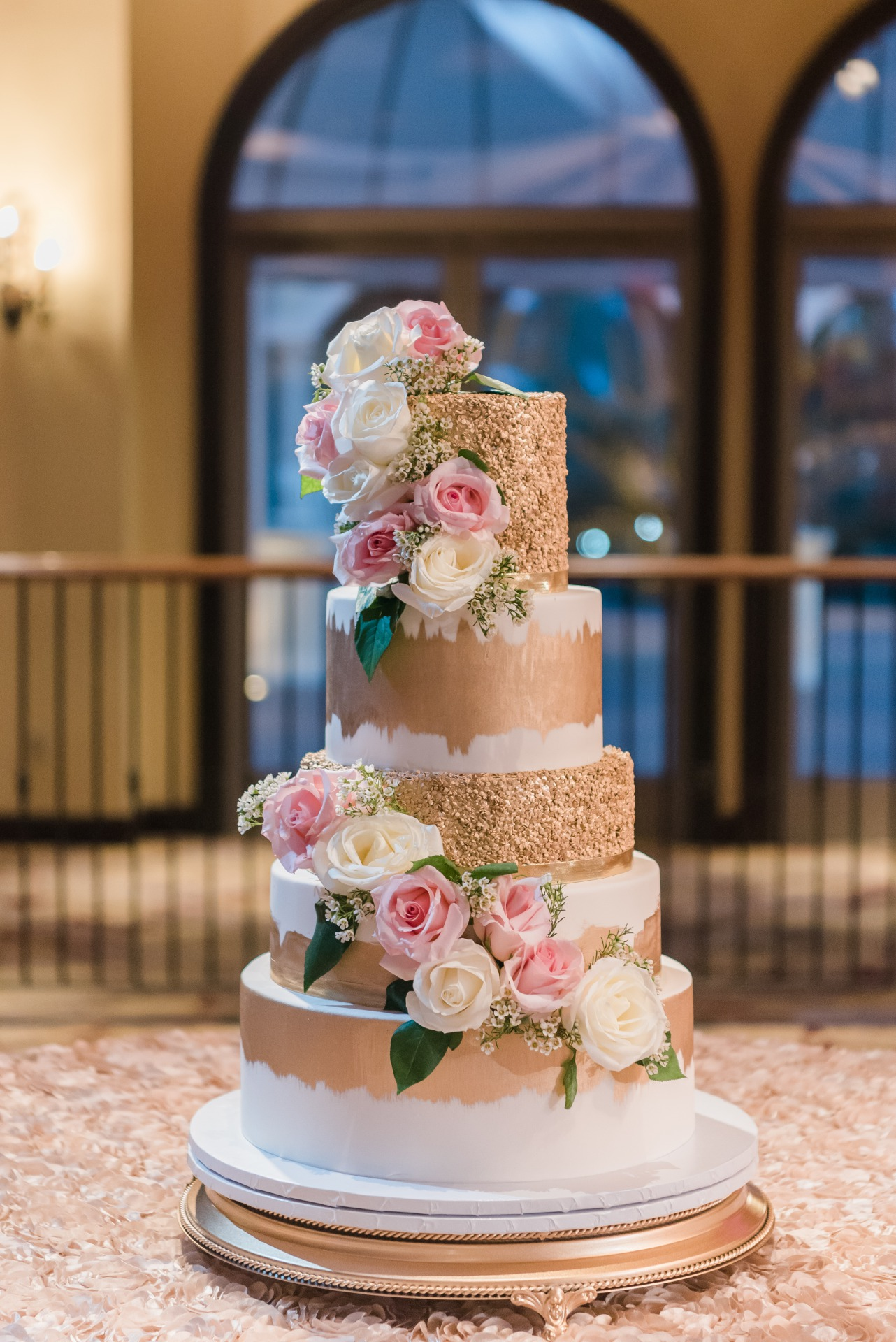 Sunning 4 tiered white wedding cake with gold shimmery accents covered in fresh roses from Las Vegas Custom Cakes.