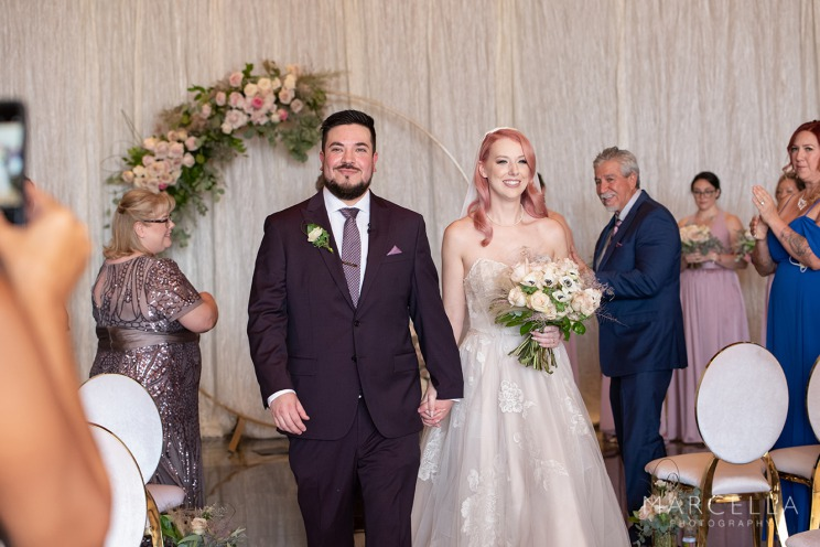 Couple walking down aisle showcasing pops of pink and purple wedding theme.