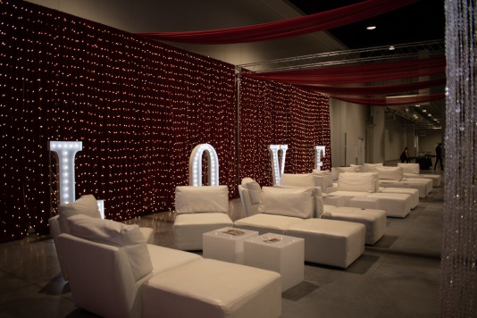 LED Unplugged Lounge twinkle lights in front of red drapes with LOVE spelled in white marquee letters and lounge furniture for weddings