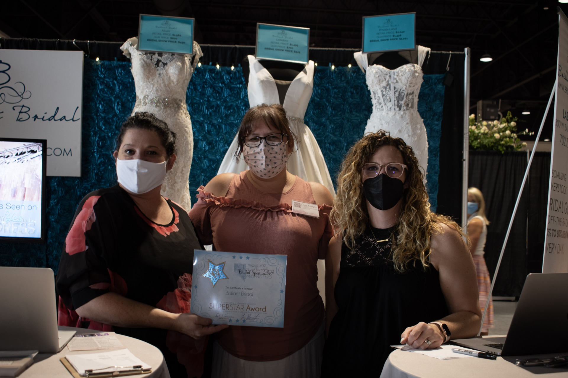 Brilliant Bridal Team members pose for a photo with their star award and Bridal Spectacular wedding expo VP Laura Covington, Las Vegas Wedding Professionals